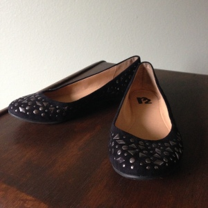 Black round toe flat with nickel finish studs.