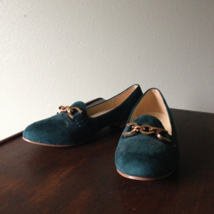 Teal loafers with gold buckle.